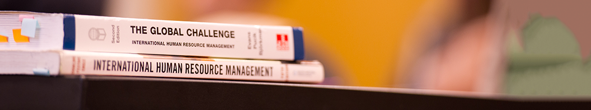 Business management books sitting on a desk in a classroom