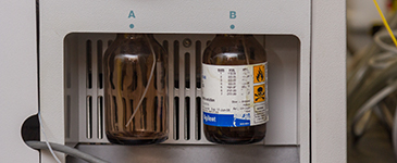 Two medicine bottles sit in a testing machine.