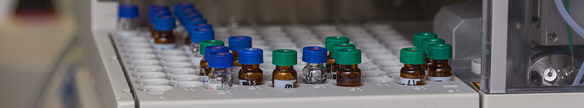 A close-up of pharmacy bottles in a testing machine.