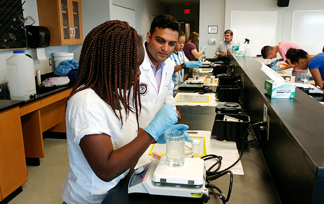 Students work in the coumpounding lab with D'Youville professors.