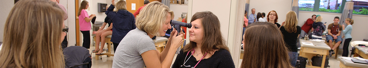 A physician assistant instructor demonstrates how to check a student's eyes.