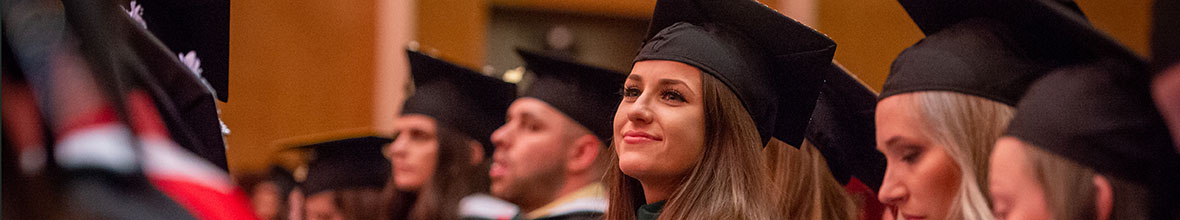 A D'Youville grad looks up proudly with the rest of her classmates  at graduation.