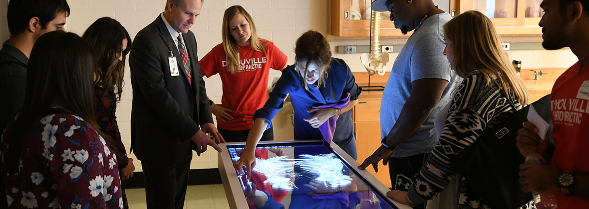 A D'Youville chiropractic student explaining the capabilities of the Anatomage table.