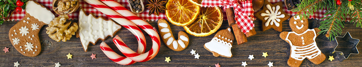 Holiday treats and goods, such as gingerbread, candy canes, and winter berries laid out on a wood table.