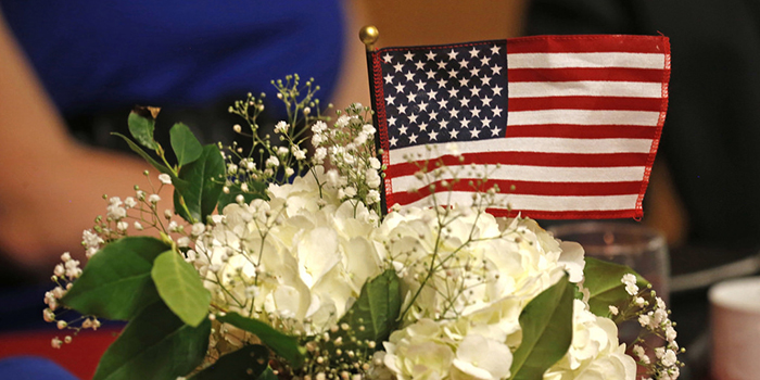 A flag rests among flowers.