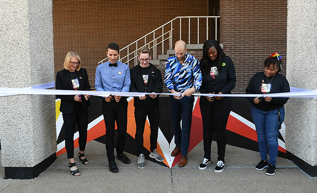 Casey Milbrand, along with student Matt Wild, and other representatives from D'Youville, cut the ribbon of the As Is mural.