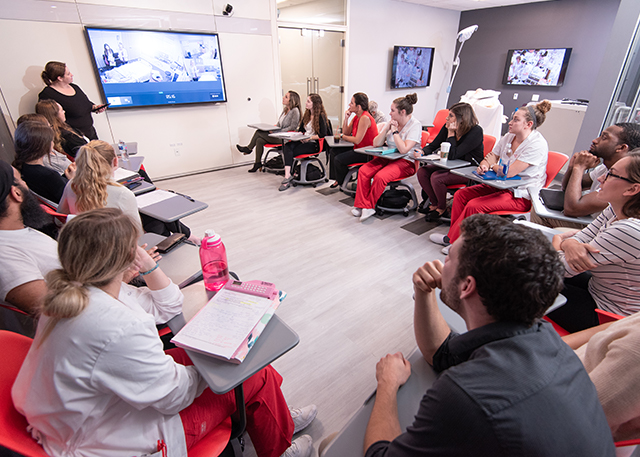 Students watch an instructor in the Simulation Center.
