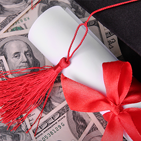 Photo: Mortarboard tassel and ribboned scroll atop a background of $100 bills