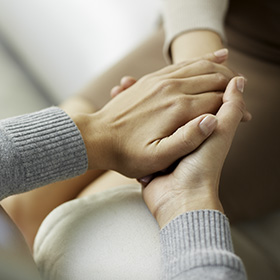 Photo: A close-up of two people holding hands.