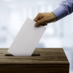 Photo: A person drops a ballot into a box.
