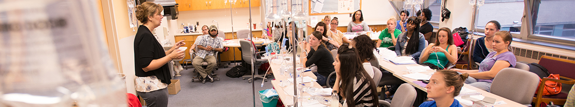 Nursing students listen intently as a D'Youville instructor lectures to her classroom.