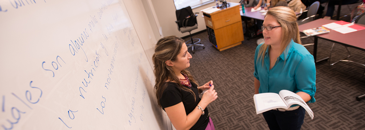 Professor Paola Kersch speaks with a student.