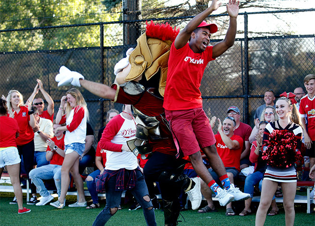 A D'Youville student and the Saint mascot celebrate at a soccer game.