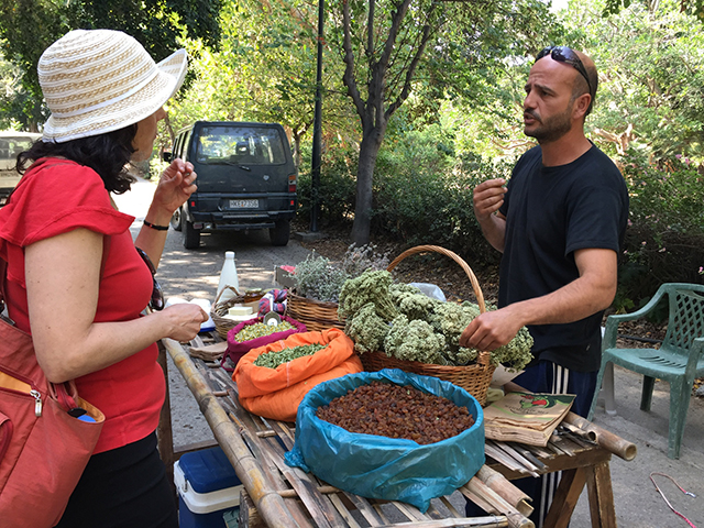 Lisa Rafalson, PhD, chair and associate professor of the Health Services Administration department, spoke with a farmer in Archanes who brought dried herbs such as oregano and lavender, raisins, plus donkey milk soap.